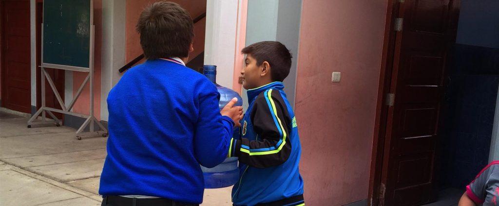Dos niños de la escuela llevando una garrafa de agua óptima para consumo a su aula.